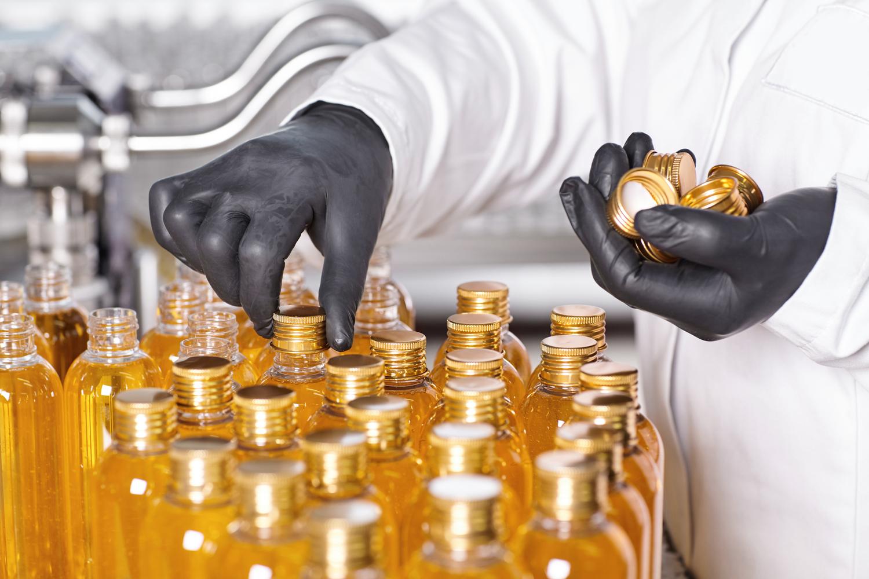 A imagem mostra uma pessoa em uma fábrica, vestindo jaleco branco e luvas de plástico. Ela está fechando diversas garrafas de plástico que contêm um líquido amarelado.
