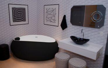 A imagem mostra um banheiro com uma banheira oval preta, em material que a deixa fosca. A banheira está instalada no canto entre duas paredes. Ao lado direito dela, há uma cuba preta, instalada em um gabinete branco.
