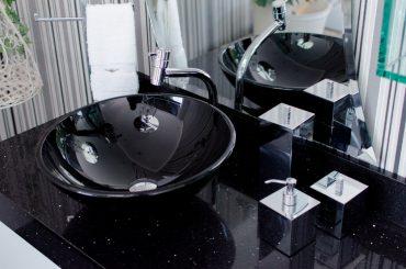 A imagem mostra uma cuba de vidro preta instalada em uma bancada de banheiro, que também é preta.