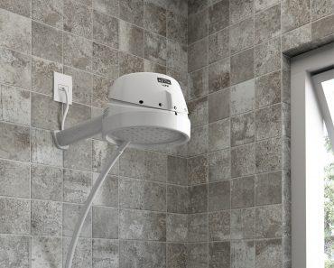 A imagem mostra um chuveiro elétrico da Astra, produzido em plástico branco. O modelo possui quatro temperaturas e está instalado em um banheiro com revestimento no tom cimento queimado.