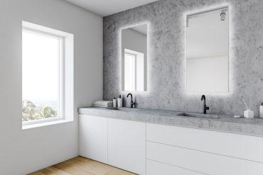 Ambiente com dois espelhos quadrados com iluminação ao redor um ao lado do outro, localizados em cima de uma pia de banheiro. O banheiro possui paredes de mármore cinza