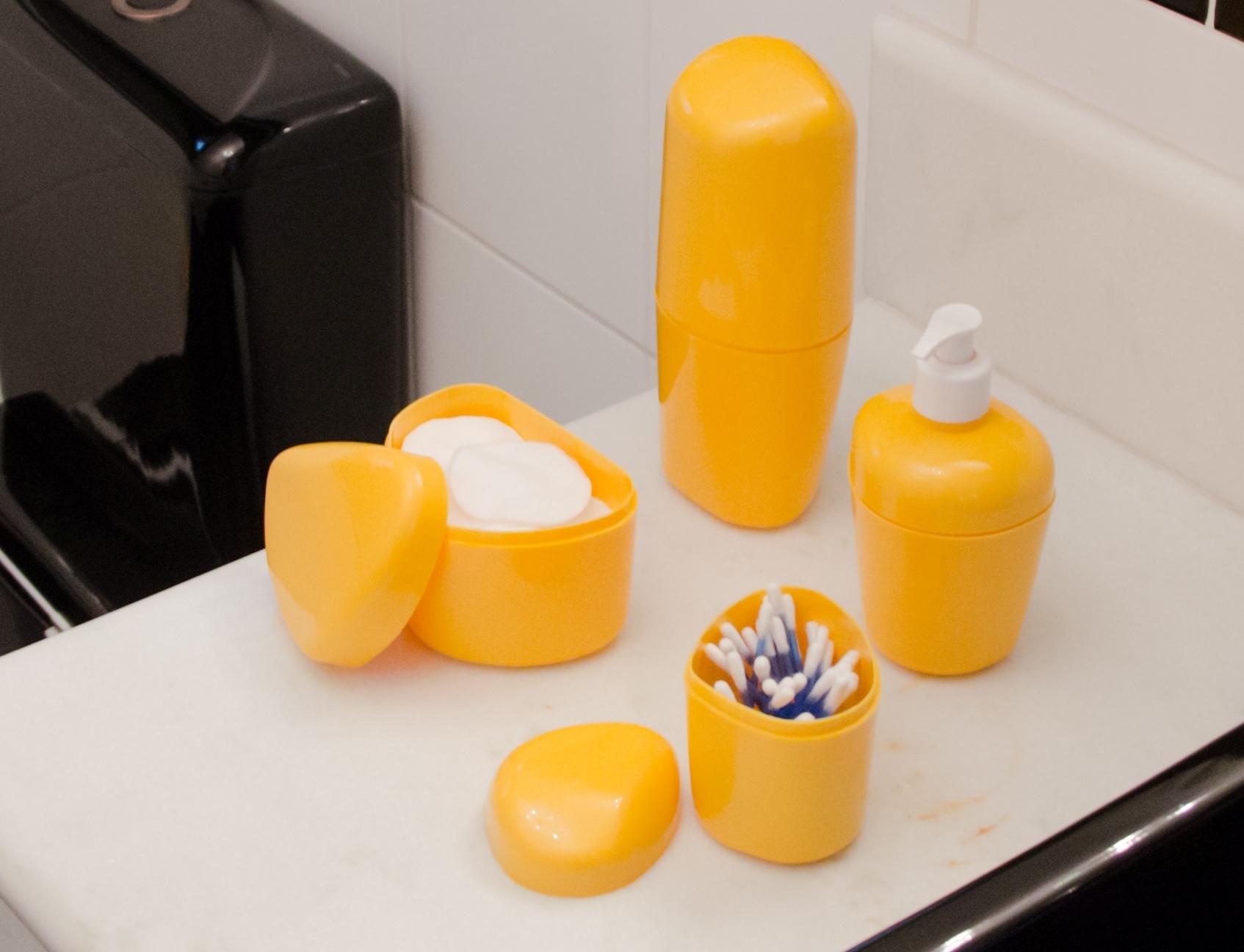 A imagem mostra uma pia com quatro elementos em cima dela, todos na cor amarela. Há um porta-cotonetes, um porta-algodão, um porta-sabonete líquido e um porta-escova.