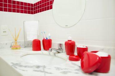 A imagem mostra a bancada de uma pia de banheiro. Em cima dela é possível ver um porta-escovas, um porta-sabonete líquido, um porta-cotonetes e um porta-algodão da Astra. Todos eles são vermelhos. Além disso, também é possível ver um difusor de ambientes e um porta-toalhas apoiados sob a bancada.