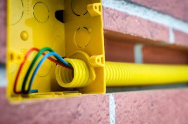 A imagem mostra uma caixa de luz ainda na fase de instalação da rede elétrica da residência, antes de finalizar a construção. Nela, é possível ver os fios que ligarão uma das tomadas da casa.