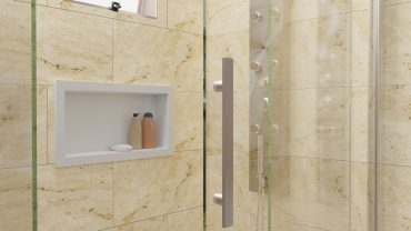 A imagem mostra um nicho embutido branco instalado na parte de dentro de um box de vidro. O nicho acomoda dois frascos de tom amarronzado e uma barra de sabonete branco. Ao lado do nicho, há um painel de banho que reflete no vidro. Acima, é possível encontrar uma janela. A parede é amarelada.