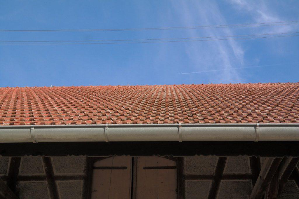 A imagem mostra parte de um telhado, principalmente as calhas instaladas na beiral dele.