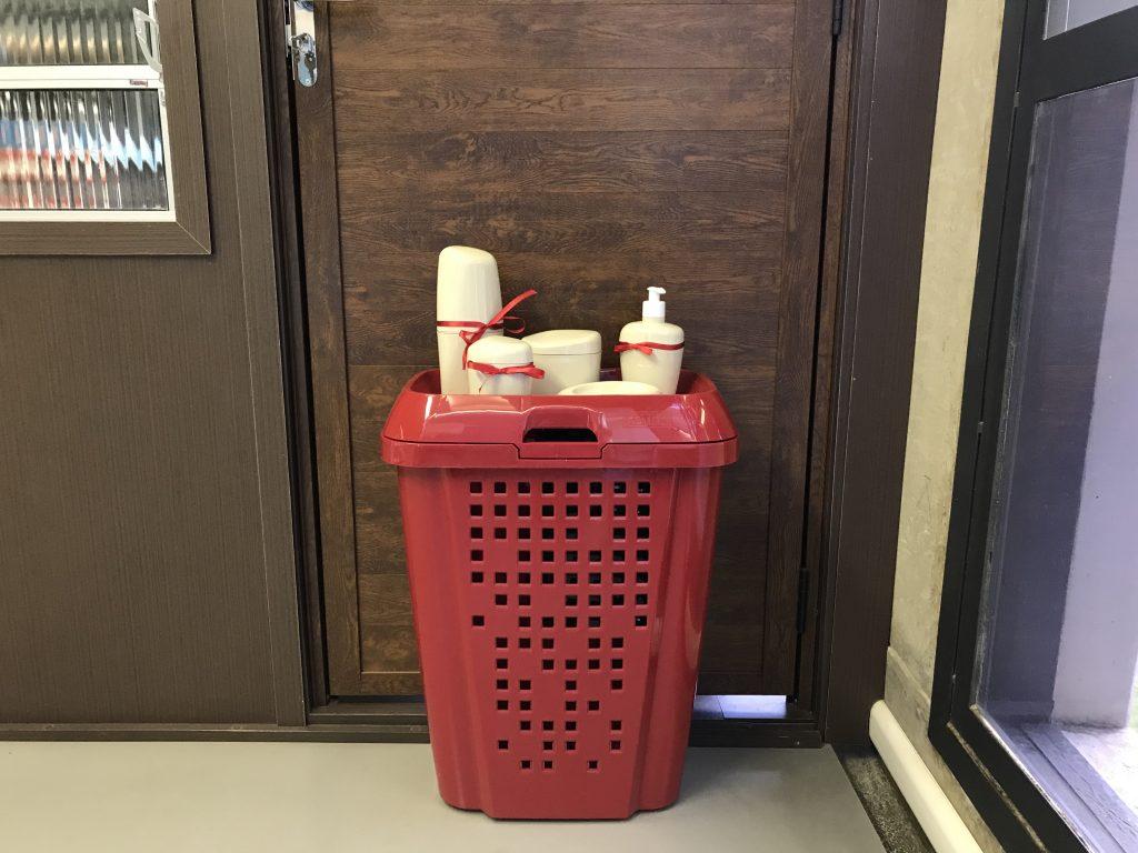 Na imagem um cesto de roupa vermelho aparece na frente de uma porta marrom. Em cima dele há itens de organização de banheiro na cor bege, todos os itens estão envolvidos por um laço vermelho.