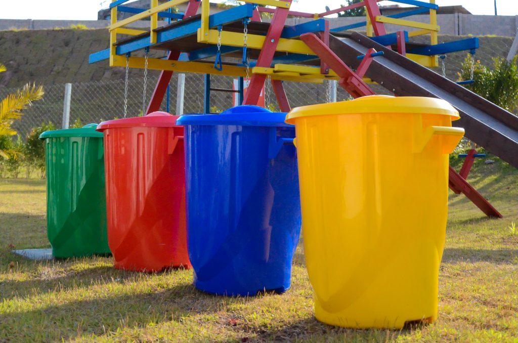 Na foto, é possível ver quatro lixeiras em um jardim, ambas para separar os tipos de reciclagem. Elas estão lado a lado, em uma fila. Da direita para a esquerda, está a lixeira amarela, a azul, vermelha e verde. Ao fundo é possível enxergar um parque infantil.