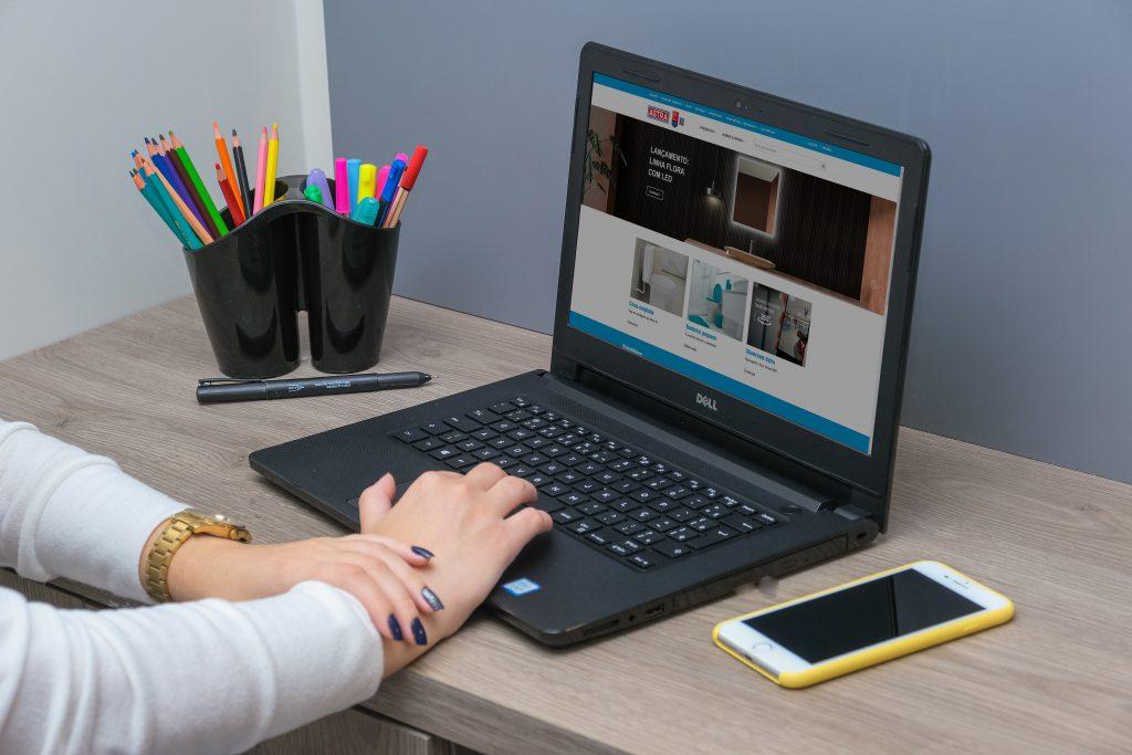 Na foto uma mão mexe em um notebook, a tela de navegação é o site institucional da Astra. O computador está sob uma mesa de madeira clara, junto à um celular de capinha amarela e um porta-objetos que acomoda canetas coloridas.