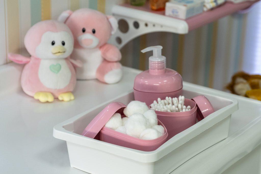 A imagem mostra a vista superior de uma bancada branca. Em cima dela, há uma caixa plástica branca, na qual é possível ver alguns porta-objetos de plástico rosas. Ao fundo, é possíver ver dois ursinhos de pelúcia, também em tom rosa.