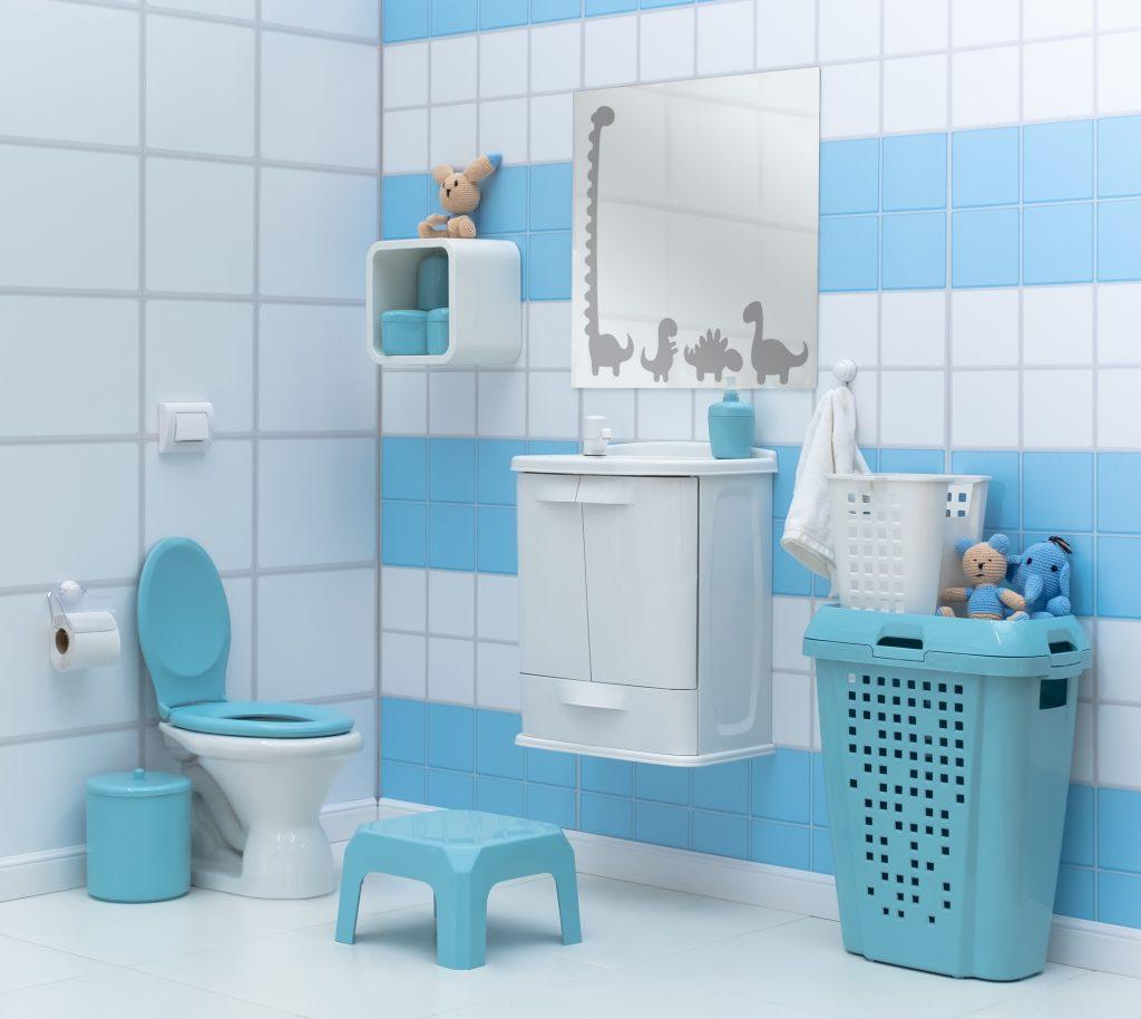 A imagem mostra um banheiro infantil. Da esquerda para direita, estão os seguintes elementos: papel higiênico em papeleira, balde de lixo azul, vaso sanitário com assento e tampas azuis, botão de descarga branco, banqueta de apoio azul. Numa outra parede, decorada com azulejos listrados horizontalmente em azul e branco, pode-se observar um nicho plástico branco, com utensílios azuis na parte interna e um boneco de pelúcia na parte superior externa, um espelho com estampas de dinossauros, uma pia branca, que possui um porta-sabonete líquido azul, toalha branca, e um roupeiro azul, que sustenta outro roupeiro branco de tamanho reduzido e outros dois bonecos de pelúcia.