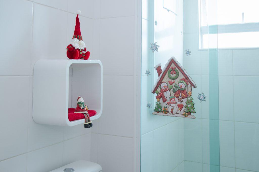 A imagem mostra a vista interna de um banheiro branco, com parte do box em destaque. Na parede que é visível fora da área de banho, encontra-se um nicho quadrado plástico, que sustenta dois bonecos natalinos, na parte de dentro e em cima, além de uma almofada vermelha em seu interior. No box, é possível ver um adesivo com temática natalina: uma casa nevada com uma família de bonecos de neve, pequenas árvores de natal, guirlandas, e algumas estrelas semelhantes a flocos de neve.