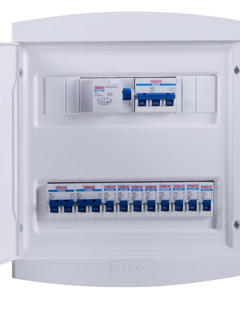 A imagem mostra um quadro de passagem da Astra aberto. Ele é branco e fabricado em plástico. No interior dele, é possível ver alguns tipos de disjuntor, também da Astra, montados. Eles possuem interruptores azuis e estão todos ligados, voltados para cima.