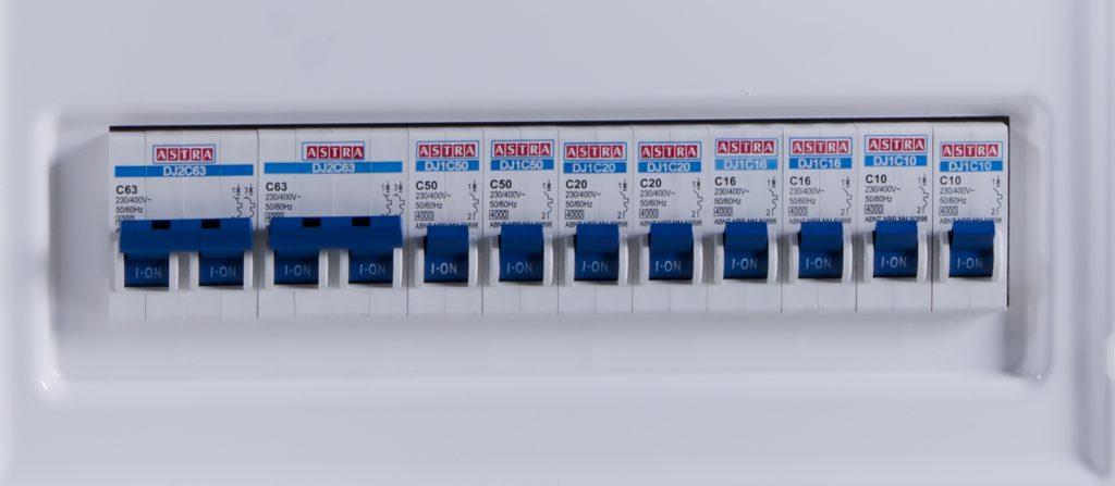 A imagem mostra alguns disjuntores da Astra montados em um quadro de passagem. Todos eles estão com os interruptores azuis ligados, voltados para cima.