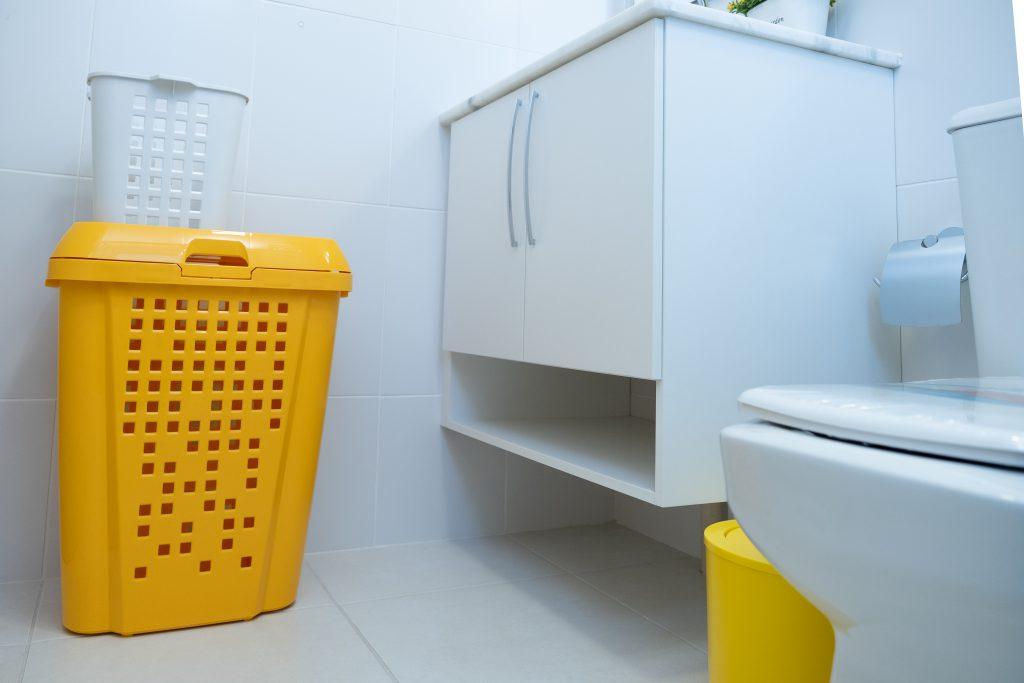 A imagem mostra um banheiro com elementos majoritariamente brancos. Da esquerda para a direita, existe um roupeiro telado amarelo, que sustenta um modelo branco de tamanho bem inferior. É possível ver uma bancada e um vaso sanitário brancos, com uma lixeira amarela entre eles. Ademais, uma papeleira prata, sem papel higiênico.