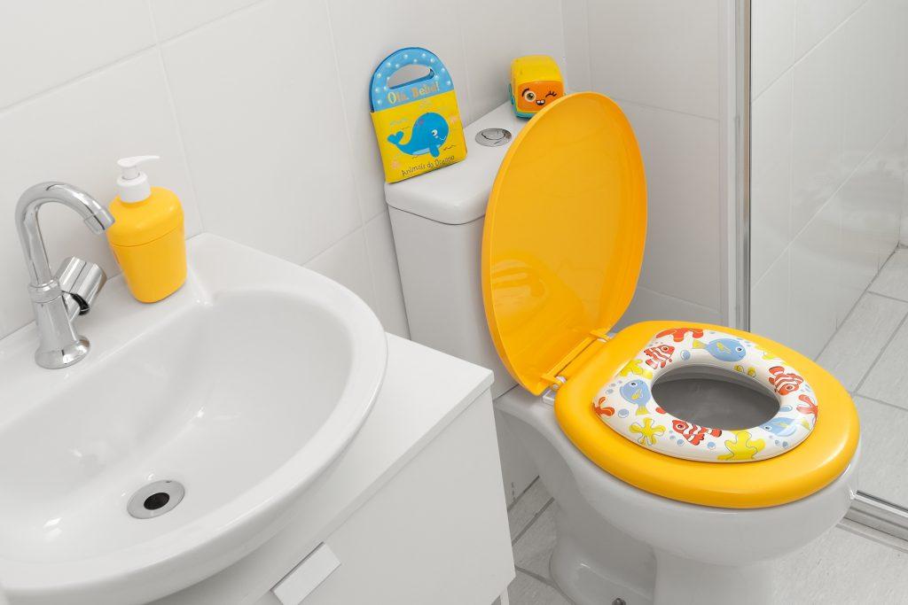 A imagem mostra a vista interna de um banheiro infantil revestido com pisos brancos. É possível observar uma pia com torneira prata, onde, no lugar da saboneteira, existe um porta-sabonete líquido amarelo. No encosto do vaso sanitário, existe um livro lúdico amarelo com uma baleia azul, e um outro um brinquedo infantil; o vaso em si é branco, com exceção da tampa e do assento, que são amarelos, e tem acoplado um redutor de assento sanitário, estampado com peixes e figuras do oceano.