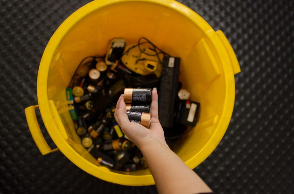 Na imagem é possível ver a mão de uma pessoa branca segurando algumas pilhas em cima da boca de um cesto amarelo. No interior do cesto é possível visualizar alguns cabos e pilhas.