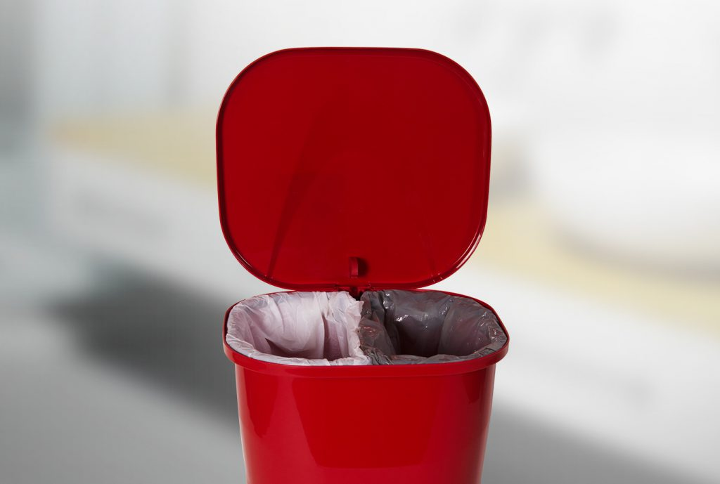 Na foto é possível visualizar uma lixeira da Astra vermelha. Sua tampa está aberta. Dentro dela há dois sacos de lixo, um branco e um preto.