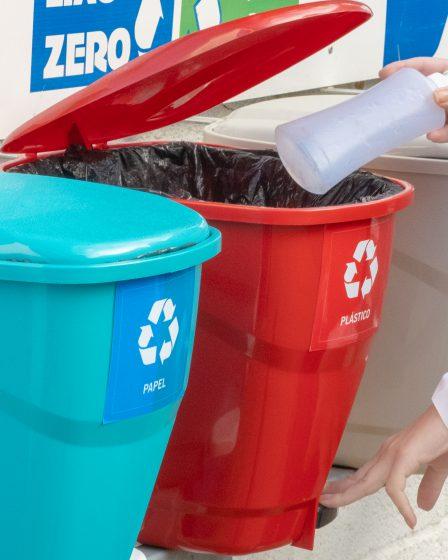 A imagem mostra cinco lixeiras coloridas, utilizadas para descartar corretamente os resíduos reciclados. Da esquerda para a direita, há uma lixeira em tom azul-claro, destinada para o descarte de papel; ao lado dela está uma lixeira vermelha, destinada aos resíduos plásticos, em seguida, há uma lixeira bege, usada para o descarte do lixo orgânico; por fim, há uma lixeira em tom verde-escuro, usada para descartar materiais não reciclados. Também é possível ver as mãos de uma pessoa branca. Com a mão esquerda, ela pressiona a alavanca que abre a lixeira vermelha. A mão direita da pessoa leva uma embalagem plástica ao interior da lixeira.