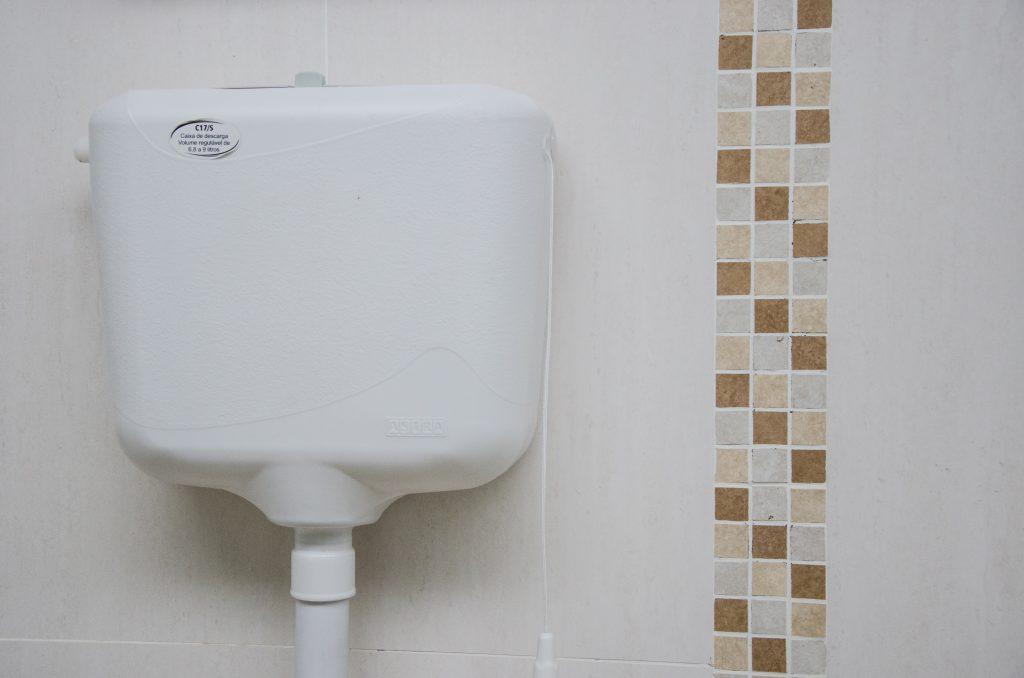 A imagem mostra uma caixa de descarga alta inteiramente branca, posicionada na parte superior de uma parede com pisos bege e azulejos decorativos.