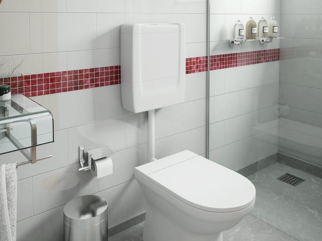 A imagem mostra o panorama interno de um banheiro bem decorado, com piso de aspecto cimentado, parede revestida com peças brancas e uma faixa de azulejos vermelhos. Da esquerda para a direita, é possível observar parcialmente uma pia de vidro, um balde de lixo de aço inox ao chão, uma papeleira prata com papel higiênico, um vaso sanitário que possui uma caixa de descarga baixa acoplada, além do box da área de banho, onde uma prateleira sustenta quatro produtos de higiene.