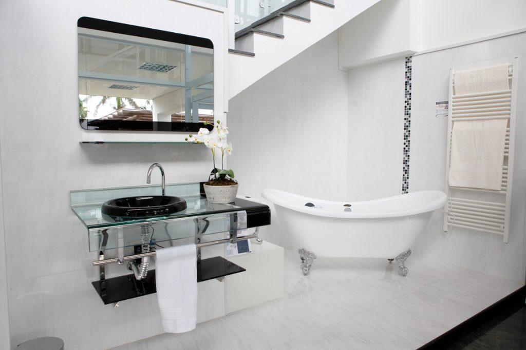 A imagem mostra, em destaque, um gabinete de vidro, com detalhes pretos, instalado em um banheiro com paredes e pisos brancos. Ao fundo, também é possível ver uma banheira branca.