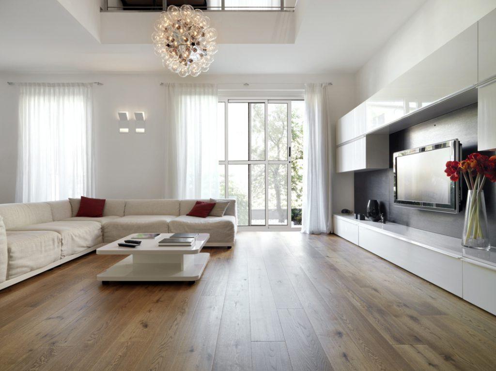 A imagem mostra uma sala de estar bem ampla, com as cores usadas na decoração minimalista. Nela, é possível ver um sofá de canto branco, uma mesa de centro branca, um rack que pega a parede direita toda, uma TV fixada na parede e um armário branco em cima dela. Também é possível ver, ao fundo, uma porta de correr envidraçada.