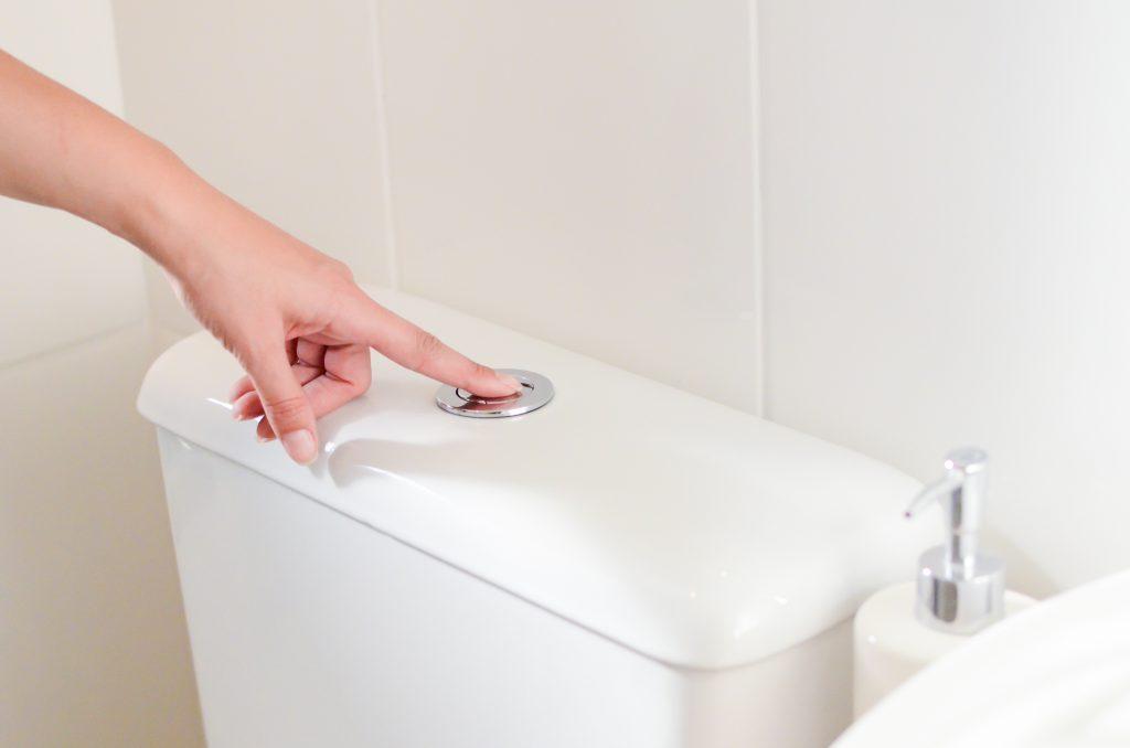 A imagem mostra uma mão feminina pressionando o botão de descarga de um sistema de caixa acoplada. Só existem elementos brancos na imagem: as paredes, a peça de cerâmica, um porta-sabonete líquido, e, parcialmente, uma parte da pia.