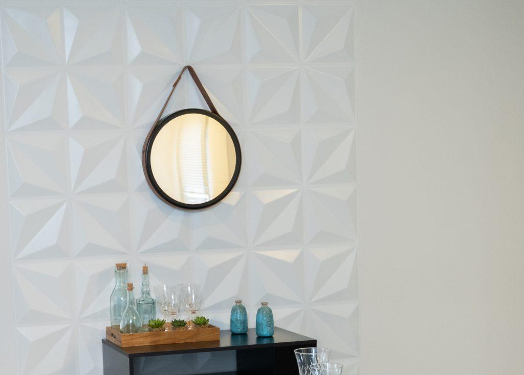 A imagem mostra um espelho oval, pendurado em uma parede branca por meio de uma alça marrom. Abaixo dele, há um móvel preto, com pequenos enfeites.