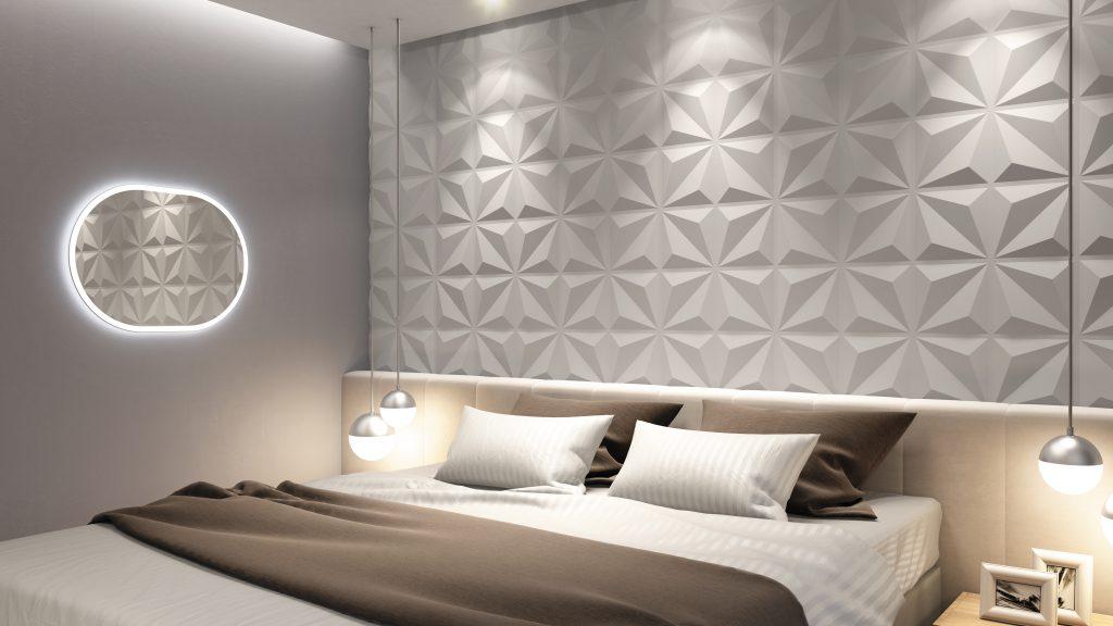 A imagem mostra um quarto. Nele, há uma cama de casal ao centro. Na parede atrás dela há revestimentos 3D brancos, que formam origamis. Também é possível ver um espelho oval com led na parede à esquerda da cama.
