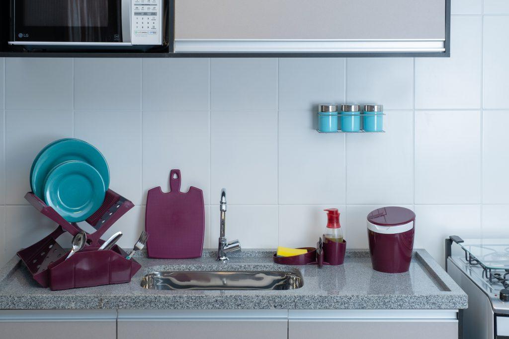 Na imagem, é possível ver a área da pia de uma cozinha. Em cima do mármore, da esquerda para a direita, há um escorredor de louças, uma tábua de corte, um porta-esponja, com espaço para colocar detergente, e uma lixeira. Todos eles são roxos.