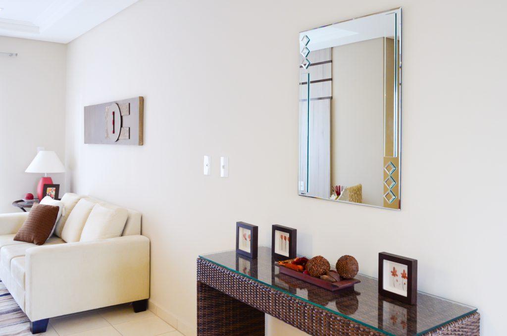 A imagem mostra uma sala de estar. Da esquerda para a direita, há um sofá branco. Na parede acima dele, é possível ver um quadro marrom. No canto direito da imagem, há um aparador marrom com o tampo de vidro. Em cima dele, há pequenos objetos decorativos na cor marrom. E na parede acima do aparador, é possível ver um espelho.