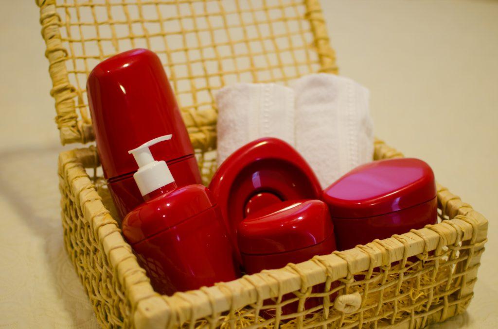 A imagem mostra uma caixa, aparentemente feita de palha. No interior dela, da esquerda para a direita, é possível ver um porta-escovas de dente, um porta-sabonete líquido, um porta-sabonete em barra e dois potes multiúso. Todos eles são de plástico vermelho. Além deles, há duas toalhas brancas, dobradas em forma de rolinho. A caixa está em cima de uma superfície branca. Esses itens de utilidade doméstica são bem comuns em listas de chá de casa nova.
