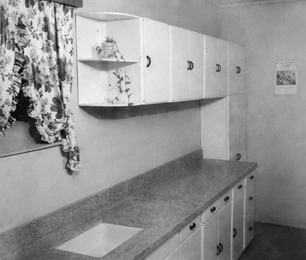 Na foto, uma cozinha com armários em madeira na cor branco.