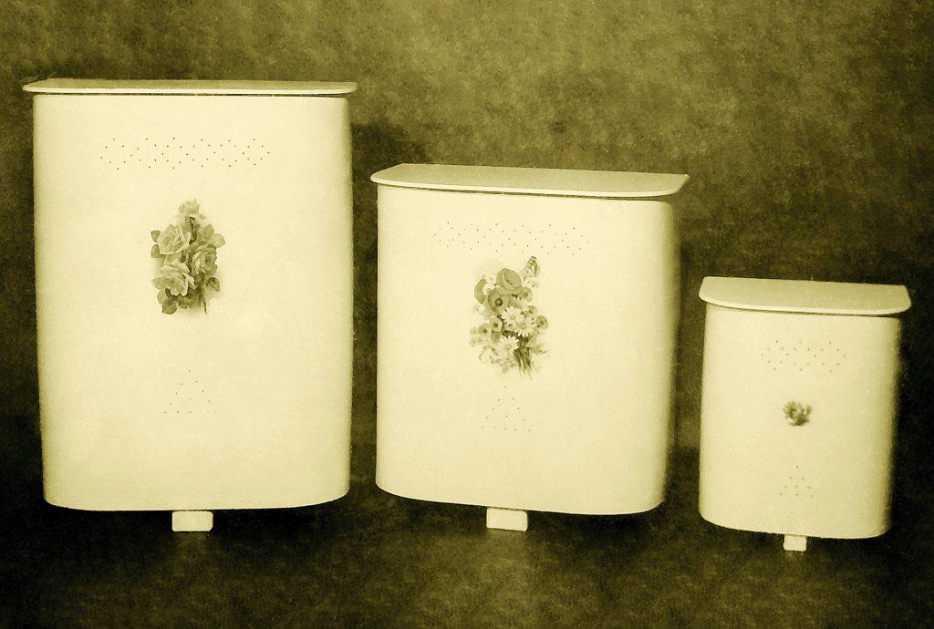 Na foto, três roupeiros de madeira da Astra. Ambos possuem uma flor como detalhe.