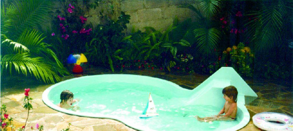 Na foto, uma piscina azul está no meio de um quintal. Nela, duas crianças brincam. Ao fundo, um jardim repleto de plantas e flores.