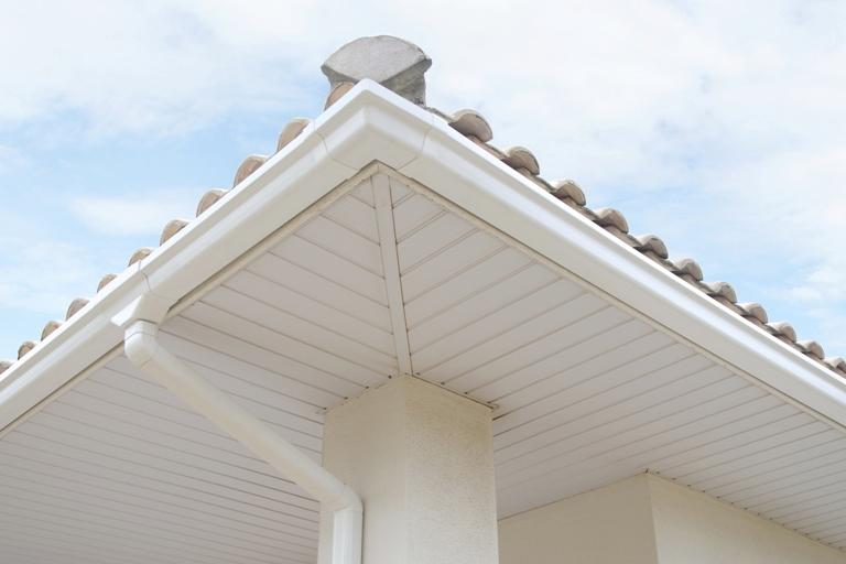 A imagem mostra um dos tipos de calhas, o de PVC, instalado ao redor do telhado de uma casa. A calha é branca e retangular. Além disso, é possível o forro da parte externa da casa, que também é branco.