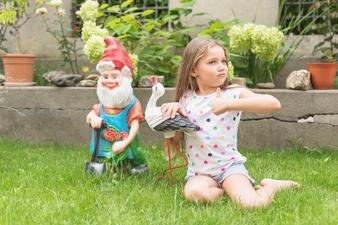 Na foto, uma criança brinca com uma ave e um duende, provavelmente de cerâmica, que estão enfeitando o jardim. Atrás dela é possível ver plantas.
