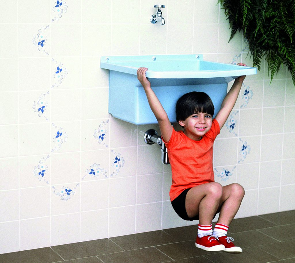 Na foto, uma criança  está pendura em um tanque de lavar roupa azul da Astra, para mostrar sua resistência. O tanque está pendurado em uma parede com azulejos bege com detalhes azul.