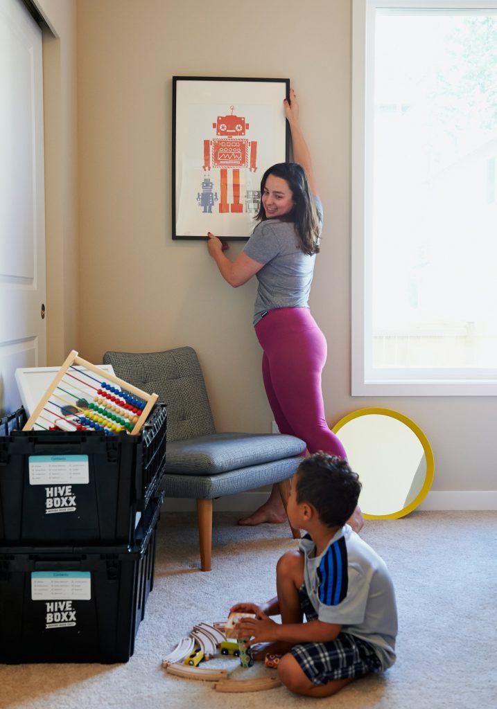 A imagem mostra uma mãe e um filho em uma sala. A mulher é branca, tem cabelo castanho-escuro liso, na altura dos ombros. Ela está em pé e ajusta o quadro de robôs na parede. O olhar dela está voltado para o menino, que está sentado no chão e brinca com alguns trenzinhos. Ao lado esquerdo do menino, há duas caixas plásticas pretas empilhadas. Na de cima, que está aberta, é possível ver um ábaco de madeira.