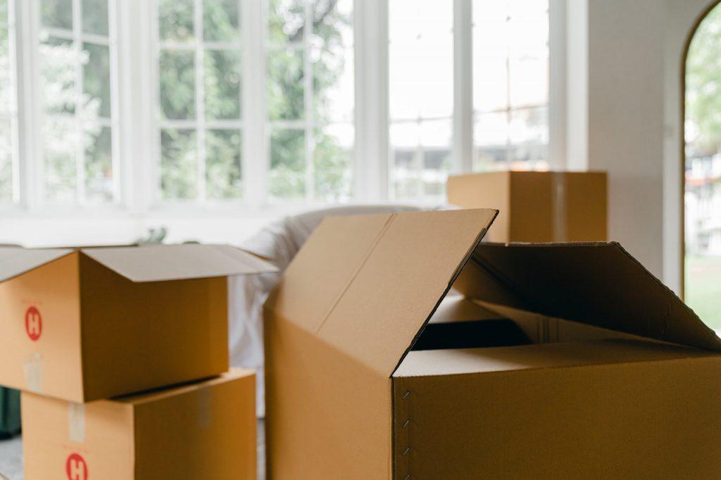 A imagem mostra algumas caixas de papelão no centro de uma sala, que parecem ser utilizadas para organizar uma mudança de casa. Da esquerda para a direita, há duas caixas de papelão pequenas, uma sobre a outra. Ao lado delas, há outra caixa maior, que está com a tampa semiaberta. Ao fundo é possível ver uma janela de vidro desfocada, que possui a estrutura metálica branca.