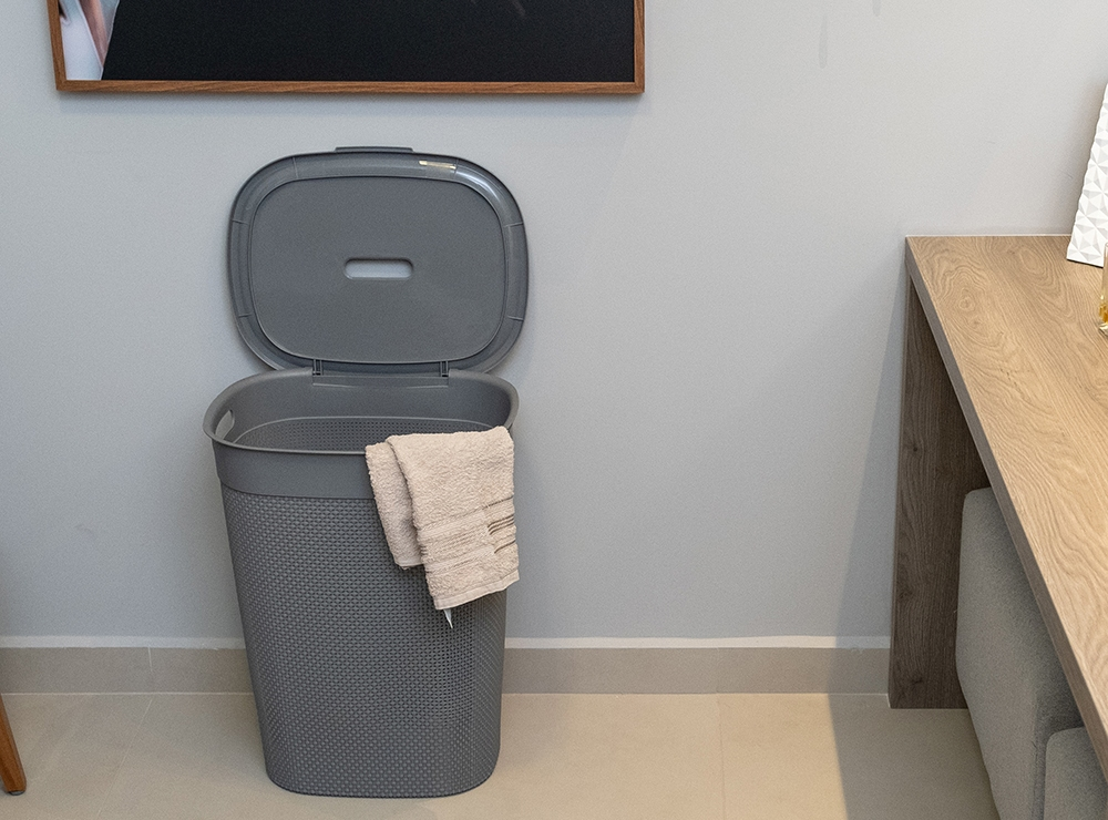 A imagem mostra em destaque um cesto de roupas cinza aberto. Ao redor dele, é possível ver uma poltrona marrom e uma mesinha marrom, na qual há alguns itens de decoração: um porta-retrato, um difusor, dois potes de vidro e uma caixa.