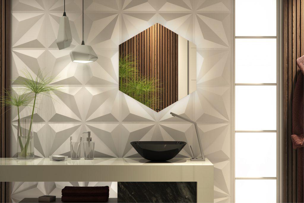 Uma cuba de apoio preta aparece sobre uma bancada de mármore branco. Ao fundo, há uma parede com revestimento 3D branco e um espelho hexagonal.