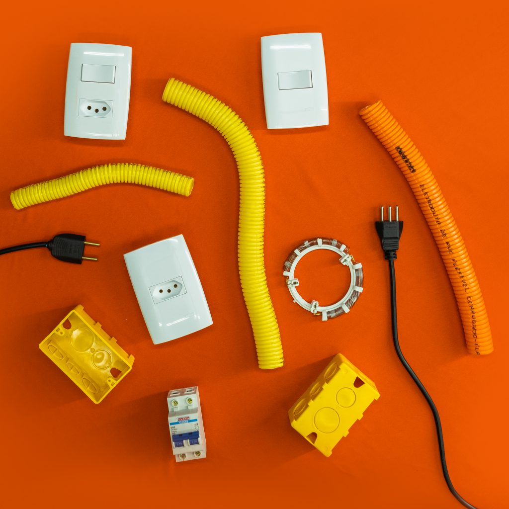 Alguns itens de elétrica aparecem sobre uma superfície laranja. Dentre eles, há tubos amarelos e laranja, tomadas e interruptores brancos, caixas de energia amarelas, fios pretos, disjuntor e resistência elétrica.