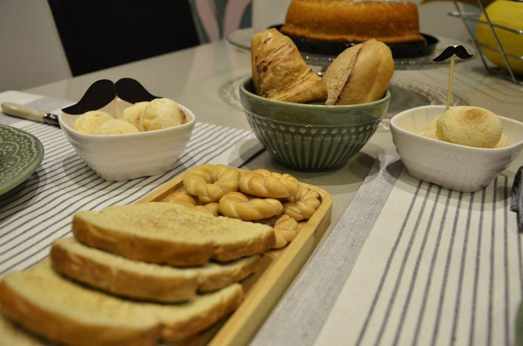 Em uma mesa, pães, pães de queijo e bolachinhas recheiam a mesa de café da manhã.