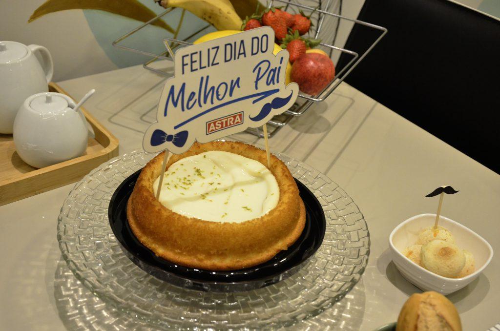 Na foto, um bolo leva uma plaquinha escrito 'Feliz Dia do Melhor Pai', ele está em cima de uma boleira de vidro. Atrás dele há uma fruteira com bananas, maça e morango, e um açucareiro.