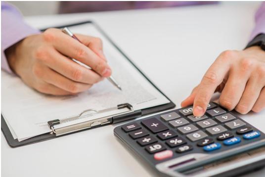 Uma mão de uma pessoa branca segura uma caneta sobre um papel branco. Com a outra mão ela pressiona a tecla de uma calculadora preta.