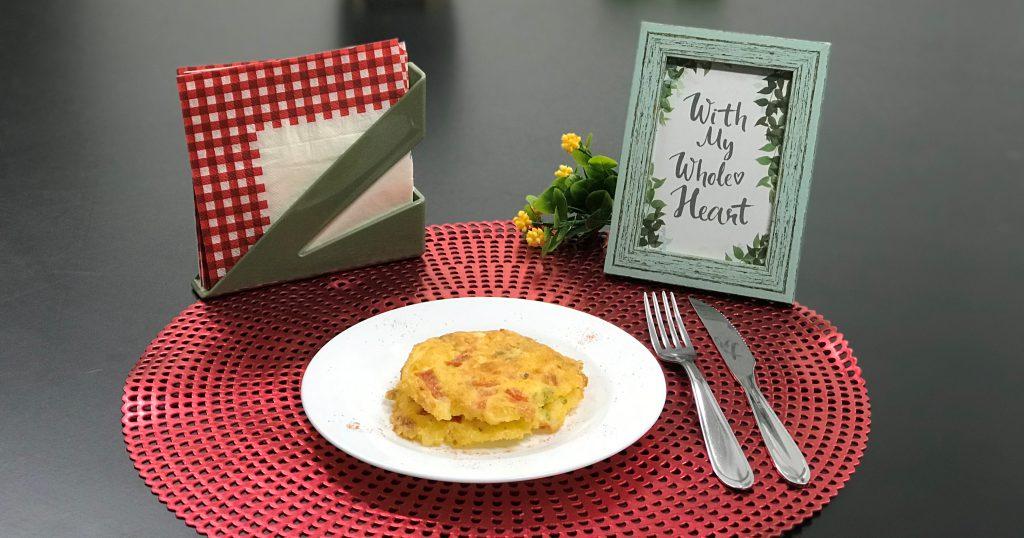 Na foto, surpresa dia dos pais, é possível visualizar em uma mesa preta um descanso de pratos vermelho, um prato branco que acomoda dois omeletes. Ao lado um garfo e uma faca prateados. Ainda, um quadro verde com uma mensagem, uma planta com flores amarelas e um porta guardanapos e guardanapos.