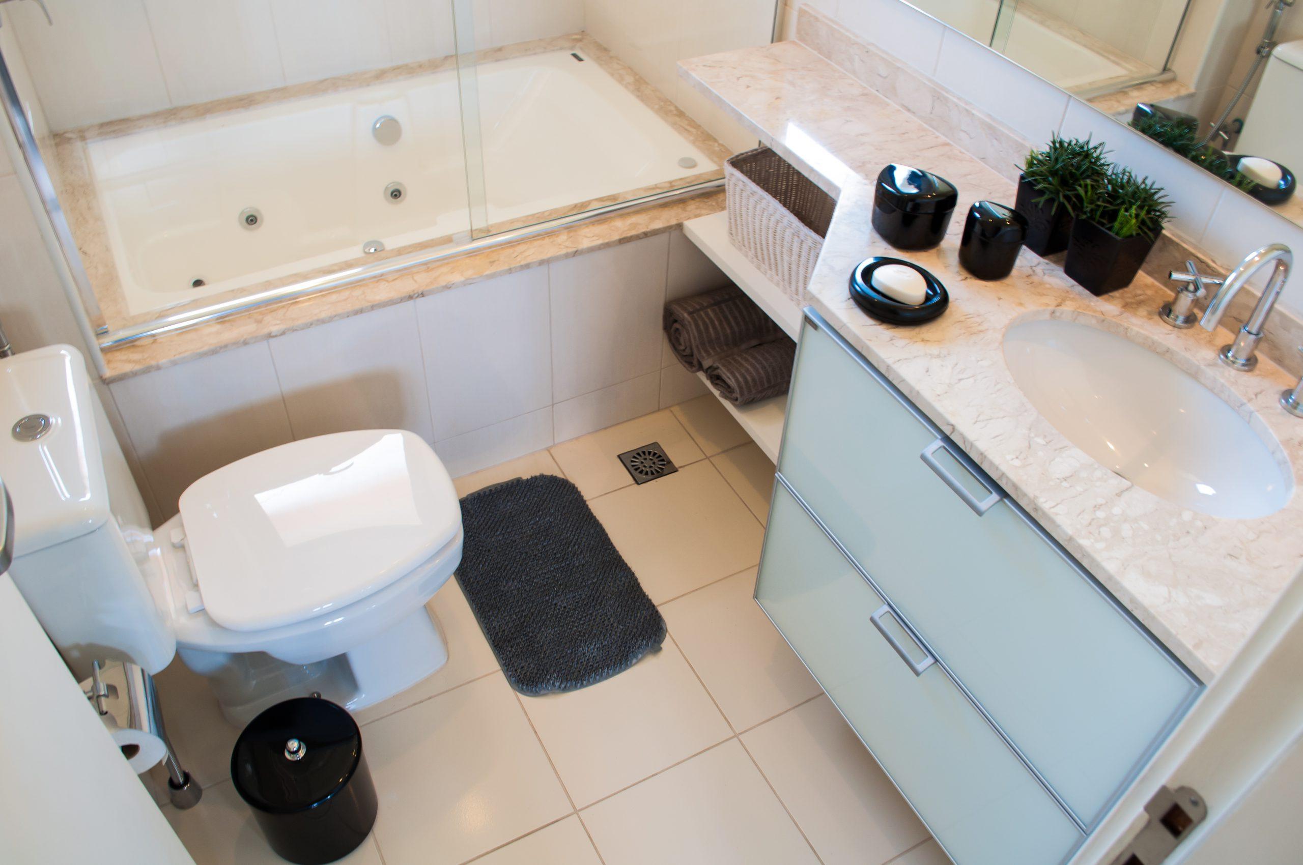 Um banheiro visto de cima, que representa uma reforma de banheiro. Da esquerda para a direita há um vaso sanitário branco, uma banheira e um box de vidro transparente. Também há um gabinete branco com acabamento em mármore claro.