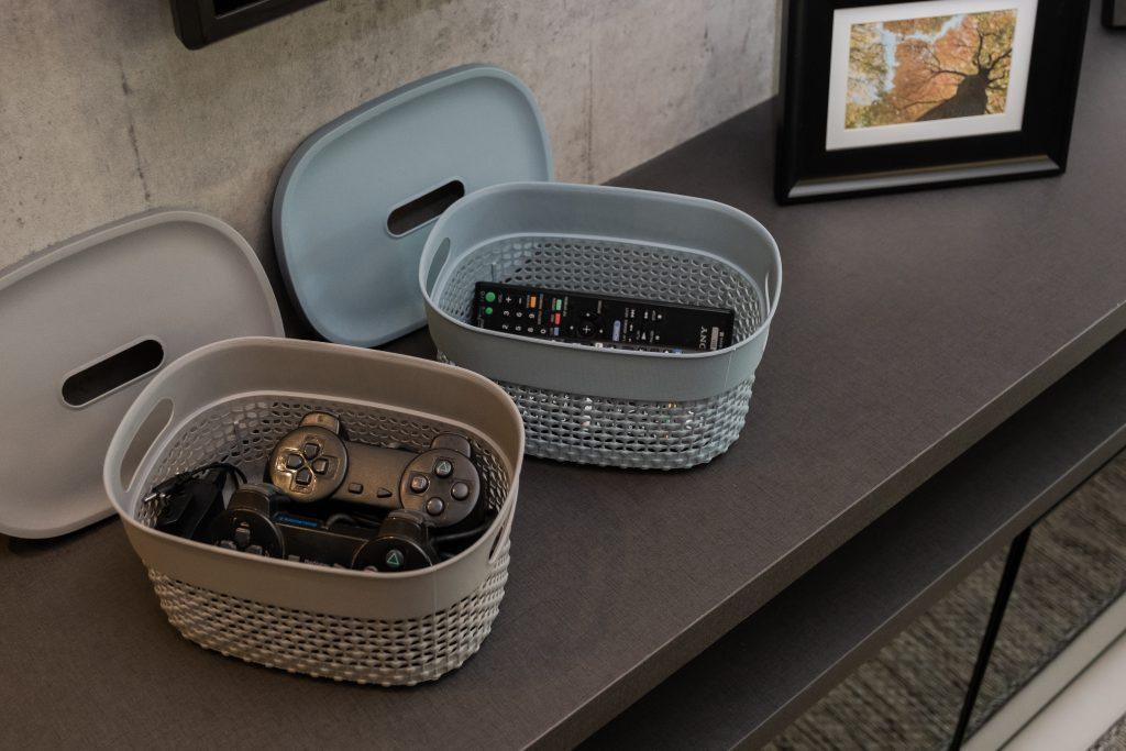 A imagem mostra duas caixas de plástico, uma cinza e outra azul, com as tampas abertas. No interior da primeira, há controles de videogame. Na segunda, é possível ver controles de TV. Elas estão sobre uma estante marrom.